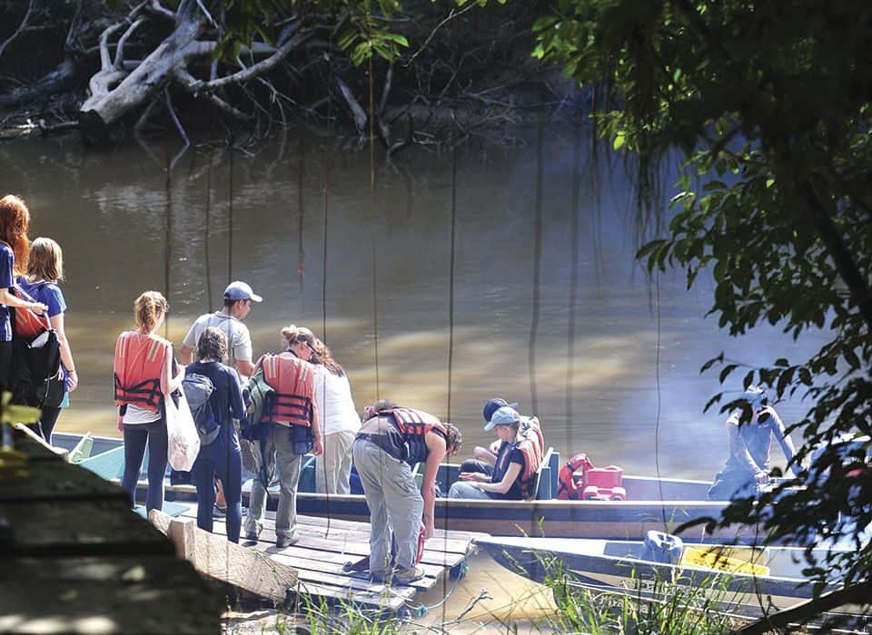 tourists taking canoes to go to cuyabeno lodge